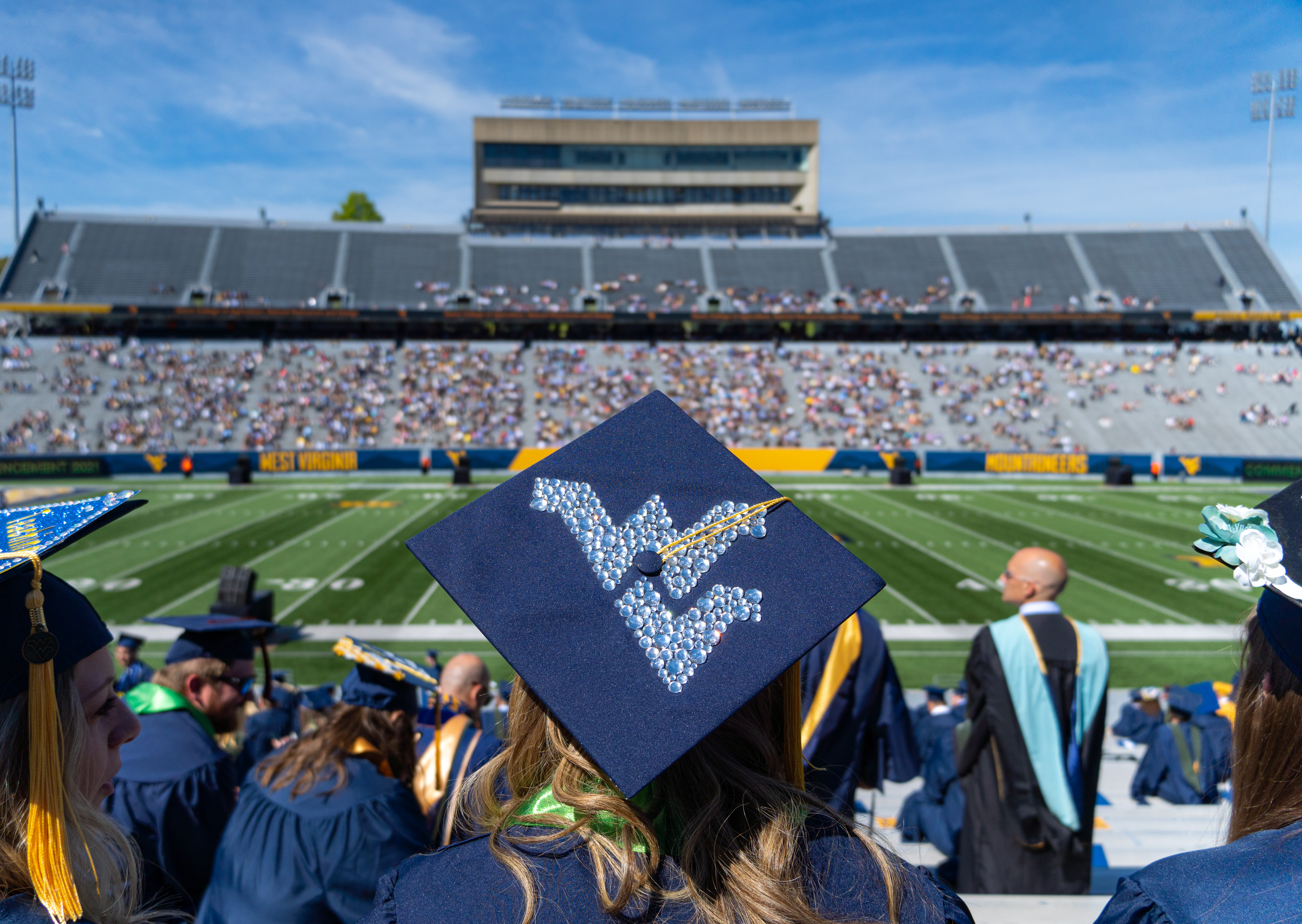 A student wears a Flying WV on a graduation cap while celebrating Commencement inside Milan Puskar Stadium, May 15, 2021.(WVU Photo/Geoff Coyle)
