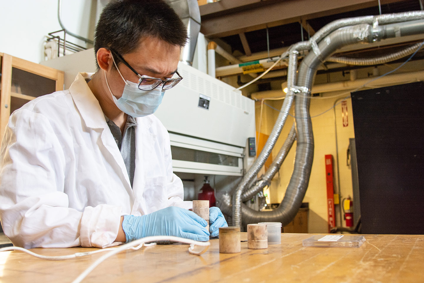 Assistant Professor Wenyuan Li assembles a solid oxide electrolysis cell, a device   that uses electricity to split water into hydrogen and oxygen to generate green,   high purity hydrogen, to the ceramic housing. (WVU Photo/Paige Nesbit)