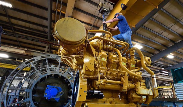 Jason England, senior laboratory instrument specialist for the Department of Mechanical and Aerospace Engineering and Center for Alternative Fuels, Engines and Emissions, prepares to lift the engine with an overhead crane to attach a generator.