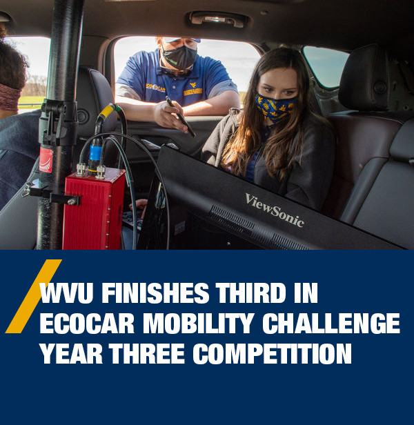 WVU finishes third in EcoCAR Mobility Challenge Year three competition - EcoCAR team members working with a monitor and equipment inside their Chevy Blazer